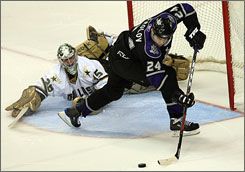 Stars goalie Marty Turco stops the progress of the Kings' Alexander Frolov during the first-round of the shootout.