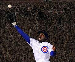 Chicago Cubs OF Felix Pie leaps into the ivy at Wrigley Field in Chicago to catch a long fly ball against the Cincinnati Reds on April 15, 2008.