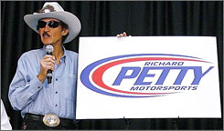 Richard Petty displays the new logo for his freshly merged team, taking cues from his former operation's logo.