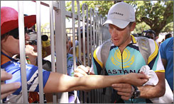 Lance Armstrong signs a fan's arm after the fourth stage of the Tour Down Under.