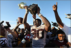 Glades Central's Artavious Dowell celebrates with the coveted trophy after the team defeated Pahokee in last year's Muck Bowl.