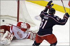 The Blue Jackets' Rick Nash celebrates his game-winning goal in overtime on Red Wings goalie Chris Osgood. The strike capped a hat trick for Nash as Columbus prevailed 3-2.