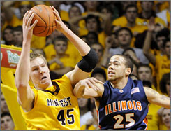 Minnesota's Colton Iverson, left, goes high for a pass as Illinois' Calvin Brock (25) and Jeff Jordan (13) defend during the first half of their game in Minneapolis. The Golden Gophers snapped a 20-game losing streak to Illinois.