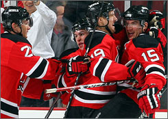Devils teammates mob Jamie Langenbrunner, right, after he scored with a minute left in overtime to defeat the Penguins 4-3. The goal was the third consecutive game-winner by Langenbrunner.