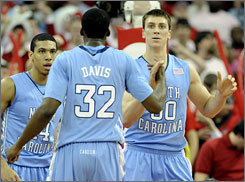 Tyler Hansbrough is congratulated by Ed Davis as Danny Green looks on as the Tar Heels pulled away late to cruise past N.C. State.