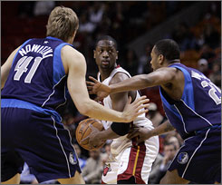 Heat guard Dwyane Wade, center, is double-teamed by Dallas Mavericks forward Dirk Nowitzki, left, and guard Antoine Wright during the first quarter of their game in Miami. Wade and Nowitzki each scored 30 points, but the Mavericks won 111-96.