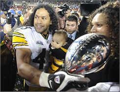 The Steelers' Troy Polamalu poses with his family and the championship trophy.