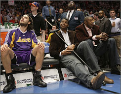 The Lakers' Andrew Bynum, center, watches from the bench with teammates during Los Angeles' win over the Knicks at Madison Square Garden. Bynum, who injured his knee Sunday, will be out for 8-12 weeks.