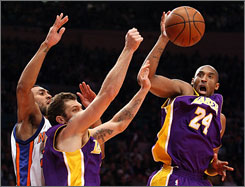 The Lakers' Kobe Bryant rebounds as teammate Luke Walton and the Knicks' Jared Jeffries look on at Madison Square Garden. Bryant finished with 61 points.