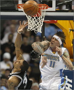 Nuggets big man Chris Andersen swats away a shot by the Spurs' George Hill during the first quarter. Denver won 104-96 but faced a stiff test from a San Antonio team playing without Tim Duncan, Manu Ginobili and Tony Parker.