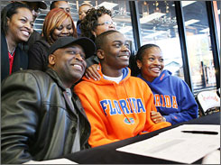 Andre Debose, in orange, is all smiles with his family after signing his letter of intent to play for Florida.