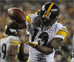 Santonio Holmes uses the football as a prop during his celebration of the game-winning touchdown at Super Bowl XLIII. Mike Pereira, the NFL's vice president of officiating, says a penalty should have been called, but that officials were already setting up for the extra point and didn't see Holmes' celebration.