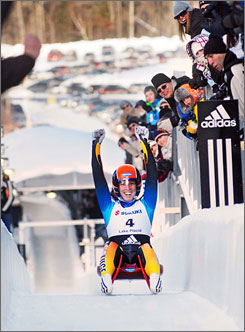 Erin Hamlin raises her arms in triumph after winning the women's luge world championships. The American's victory broke Germany's dominance of the sport, which dated to Nov. 29, 1997  a 99-race winning streak.