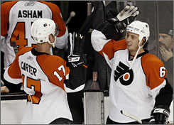 Jeff Carter and Randy Jones celebrate Jones' overtime goal that gave the Flyers a 4-3 win against the Bruins in Boston on Saturday afternoon.