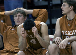 Texas' Dogus Balbay covers his face on the bench in the final moments of the 17th-ranked Longhorns' 58-55 loss at Nebraska.