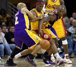 Cleveland Cavaliers guard Daniel Gibson, center, is sandwiched between Los Angeles Lakers Derek Fisher, left, and Kobe Bryant during the Lakers' 101-91 victory in Cleveland on Sunday.