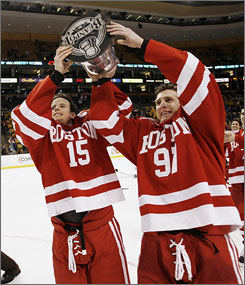 Boston University captains John McCarthy, left, and Matt Gilroy hoist the championship trophy after defeating Northeastern 5-2 to win the school's 29th Beanpot hockey title.