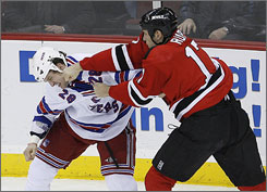 Mike Rupp of the New Jersey Devils, right, and Colton Orr of the New York Rangers fight with each other during the second period of their game on Monday night.
