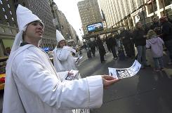 PETA supporters Caleb Wheeldon, foreground, and Andrea McIntyre hand out leaflets outside Madison Square Garden during the 133rd annual Westminster Kennel Club dog show in New York. PETA contends that the American Kennel Club promotes pure-breeding of dogs that is harmful to their health.