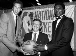 David Stern, center, holds court in one of his first official acts as NBA commissioner on June 19, 1984, presiding over the league's annual draft. He is flanked by No. 1 overall pick Akeem Olajuwon, right, and No. 2 pick Sam Bowie.