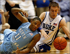 Duke's Greg Paulus, right, battles for a loose ball with North Carolina's Larry Drew during their game at Cameron Indoor Stadium in Durham, N.C. No. 3 UNC beat its most despised rival 101-87.