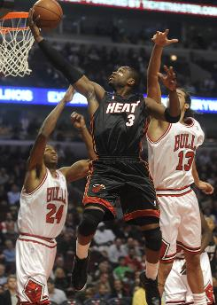 Miami Heat guard Dwyane Wade drives for a lay-up against Chicago Bulls' Tyrus Thomas and Joakim Noah en route to a 95-93 victory over his hometown Bulls.