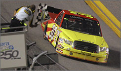 Todd Bodine's Toyota is shown the checkered flag after fending off Kyle Busch on the final lap.