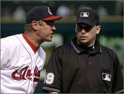In this June 20, 2001 file photo, Cleveland Indians first base coach Ted Uhlaender, left, gives umpire Andy Fletcher an ear full after being ejected for arguing a close call at first during a baseball game against the Minnesota Twins in Cleveland. 