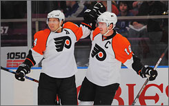 Mike Richards, right, celebrates his short-handed goal with teammate Kimmo Timonen during their 5-2 victory over the Rangers in New York on Sunday.