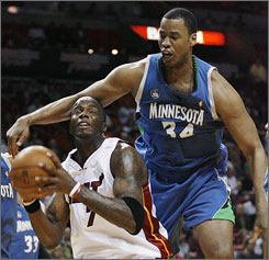 The Miami Heat's Jermaine O'Neal, left, is fouled from behind by the Minnesota Timberwolves' Jason Collins during the second quarter. O'Neal made his debut with the Heat Wednesday, but the Timberwolves spoiled the show with a 114-104 win.