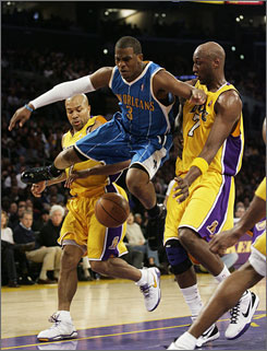 New Orleans Hornets guard Chris Paul, center, loses the ball while driving to the basket between the Los Angeles Lakers' Derek Fisher, left, and Lamar Odom. The Lakers won 115-111 in OT, snapping the Hornets' NBA-record streak of 13 consecutive overtime victories.