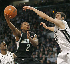 Notre Dame's Tory Jackson puts up a shot in the lane as Providence's Randall Hanke defends during the first half in Providence Jackson and the Fighting Irish cruised to a 103-84 romp of the Friars.