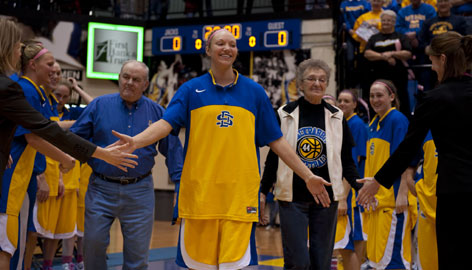 "South Dakota State's Jenn Warkenthien is introduced in her final home game Feb. 16, accompanied by her grandparents Elwood and Barbara Warkenthien. ""My grandpa taught me to have courage,"" she said. ""My grandma taught me how to be strong when it seems impossible."""