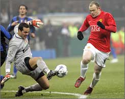 Inter Milan goalkeeper Julio Cesar kicks the ball away from Manchester United's Wayne Rooney.
