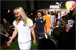 Women's Professional Soccer players show the new uniforms -- tailored to a woman's body, Commissioner Tonya Antonucci says -- Tuesday in New York.