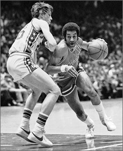 Bulls guard Norm Van Lier drives against Sixers defender Doug Collins in a March 17, 1976 matchup. Van Lier died Thursday at 61.