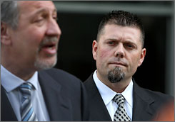Greg Anderson, right, listens as attorney Mark Geragos speaks to reporters after Friday's hearing.