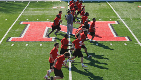 Members of the Newberry men's football team run past the giant Block 'N' that replaced an Indians-themed logo that the school gave up under pressure from the NCAA. Many at Newberry are still attached to the old nickname.