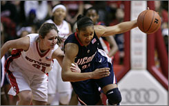 Maya Moore, dribbling the ball past Rutgers' Heather Zurich during the first half of their Big East tussle, and No. 1 Connecticut finished the regular season 30-0, including a 16-0 Big East record.
