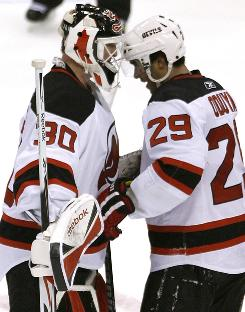 New Jersey Devils goalie      Martin Brodeur and teammate      Johnny Oduya celebrate their win after topping the Toronto Maple Leafs, 3-2.