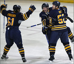 The Sabres' Maxim Afinogenov, left, and Craig Rivet, right, celebrate with Derek Roy after his second-period goal against the Canadiens. Roy scored twice as Buffalo cruised 5-1.