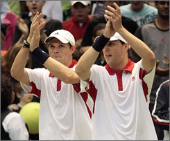 Mike, left, and Bob Bryan celebrate after beating the Swiss duo of Yves Allegro and Stanislas Wawrinka to give the U.S. a 2-1 lead in their Davis Cup tie.