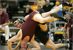 Wrestlers from the University of Iowa and the University of Minnesota grapple during a match earlier this year.