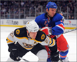 New York's      Sean Avery and Boston's      Andrew Ference battle for the puck Sunday.