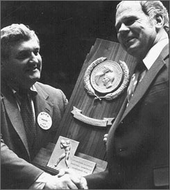 Wayne Duke, the selection committee chairman in 1979, gives Michigan State coach Jud Heathcote the NCAA championship trophy after the Spartans took down Indiana State.