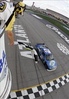 Kurt Busch takes the checkered flag to win the Kobalt Tools 500 at Atlanta Motor Speedway in Hampton, Ga., on Sunday