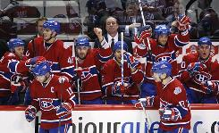Montreal Canadiens general manager and coach Bob Gainey and his squad celebrate a goal by Saku Koivu that sent the game into overtime. Koivu would score again in the overtime period to give the Habs a 4-3 win.