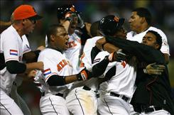 Yurendell DeCaster of the Netherlands is mobbed by his teammates after driving in the the winning run on an error by        Willy Aybar of the Dominican Republic in the eleventh inning of their World Baseball Classic game at Hiram Bithorn Stadium Tuesday night in San Juan, Puerto Rico.