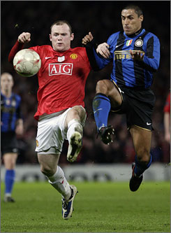 Manchester United's Wayne Rooney, left, and Inter Milan's Ivan Cordoba fight for the ball during their Champions League match in Manchester, England. Manchester United advanced to the quarterfinals with a 2-0 win.