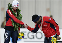 Trevor Marsicano, left, is congratulated on the podium by teammate Shani Davis after winning the 1,000 meter world championship in Vancouver on Friday.